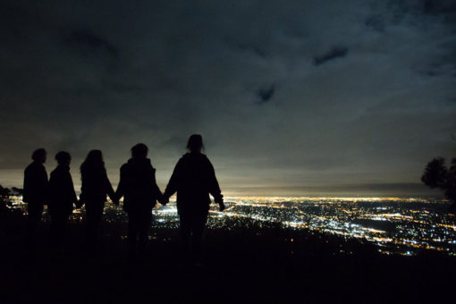 Night view of Melbourne from Mt Dandenong with a family holding hands ©Erika's Way Photography