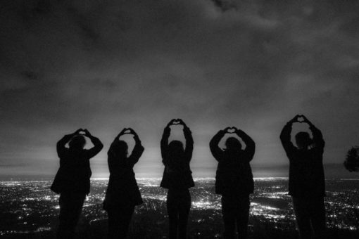 Family drawing hearts in the air in front of the skyline of Melbourne by night ©Erika's Way Photography