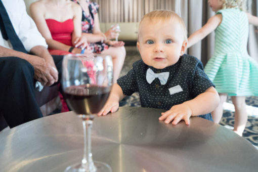 One year old kid reaching for a glass of wine. Funny candid shots at the Engagement Party. Copyright Erika's Way Photography