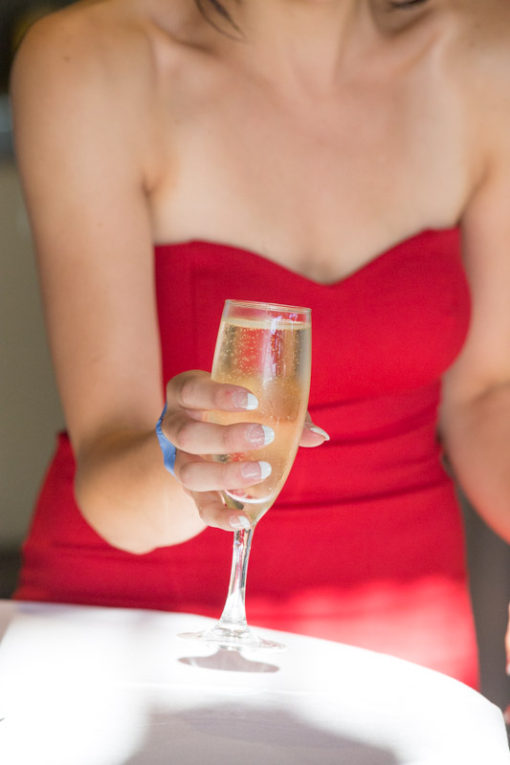 Woman in elegant red dress with a glass of champagne in her hands. Engagement photo shooting session candid shot. Copyright Erika's Way Photography. Wedding and Engagement Photographer