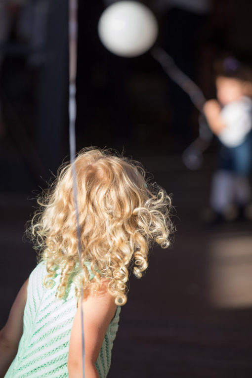Girl with blonde curly hair playing. Copyright Erika's Way Photography