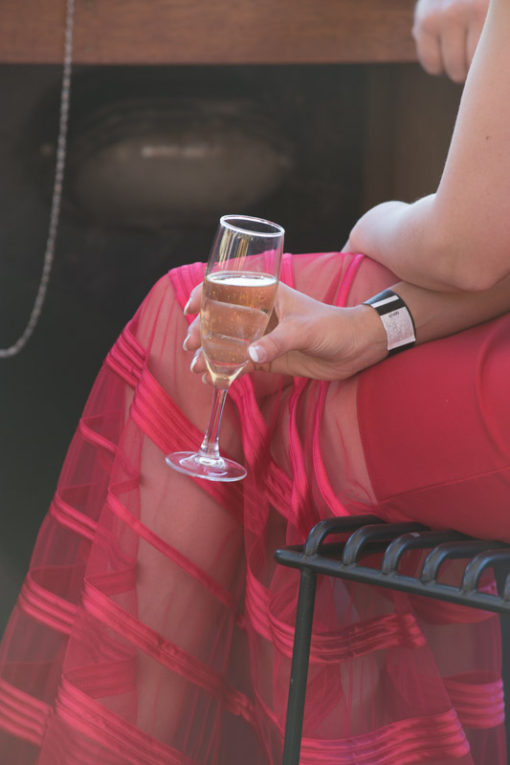 Woman in a beautiful red dress and with a glass of champagne