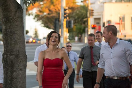 Bride laughing with bridesmaids and groomsman in a street in Frankston