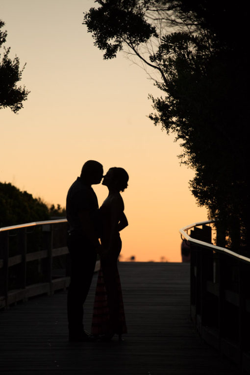 Engagement couple Photography in Frankston and Mornington Peninsula. Couple hugging and kissing in the sunset near the beach. Copyright Erika's Way Photography Wedding and Engagement Photographer in Melbourne