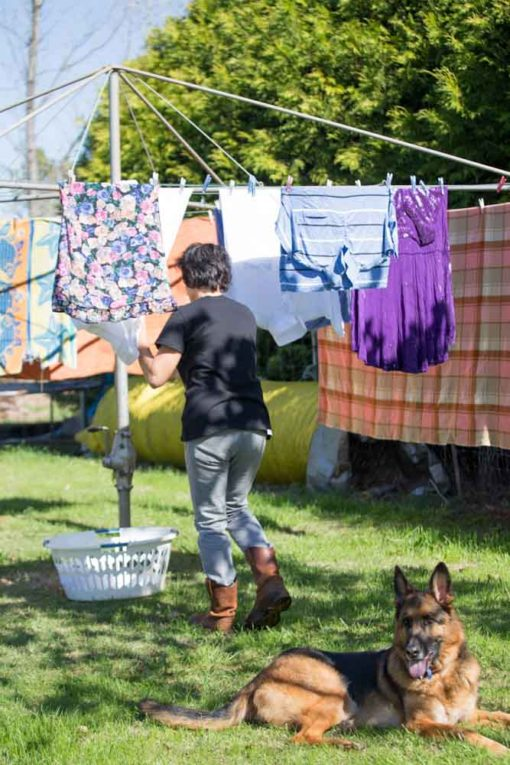 Farmer drying the laundry at the sun with her loyal dog