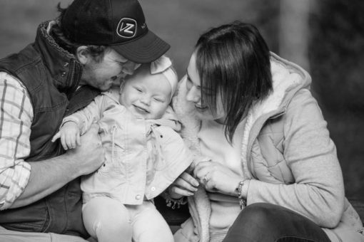 Mum and Dad and baby daughter cuddles in the park. Natural light, lifestyle Photography by Erika's Way Photography
