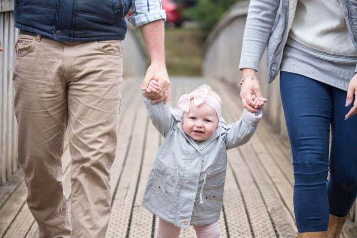 Mum and Dad and one year old daughter walking together. Copyright Erika's Way Photography