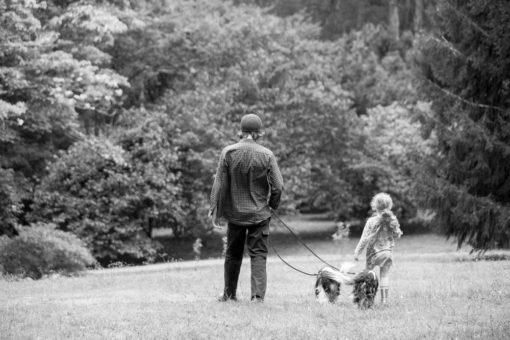 Father and daughter walking together with the family dogs in a park in the Dandenong Ranges