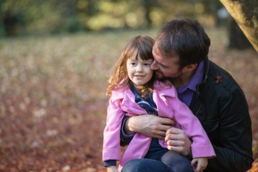 Father gently kissing and hugging his daughter at Alfred Nicholas Garden
