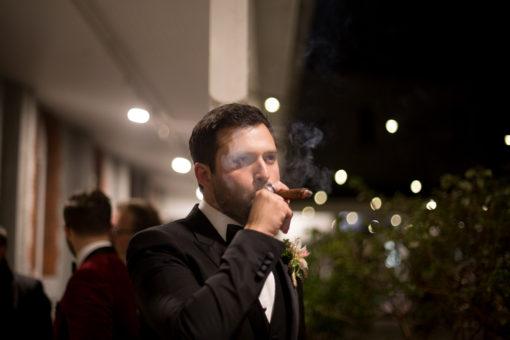 Groom smoking a cigar at his Wedding