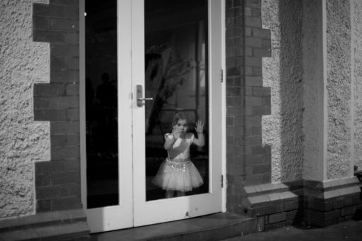 little girl looking through the door happy and tired after the Wedding Day