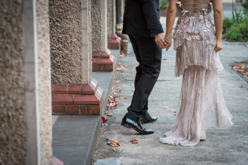 Bride and Groom walking hand in hand along the courts of Abbotsford Convent. Erika's Way Photography