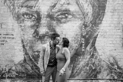 Kissing photo in front of a big Mural. Couple photography in Fitzroy, Melbourne. Photo by Erika's Way Photography