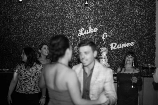 Luke and Ranee dancing at their Engagement Party with their names on the wall in the background. Photo by Erika's Way Photography