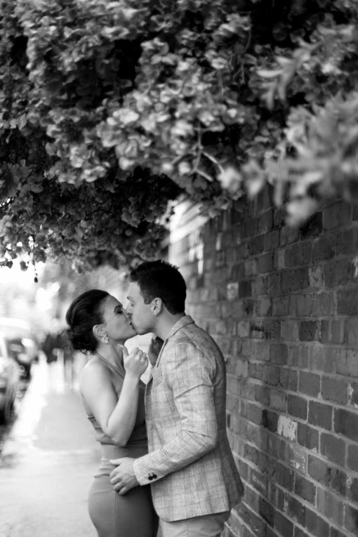 Romantic and funny kissing moment under a light rain. Street Photography in Melbourne. Photo by Erika's Way Photography